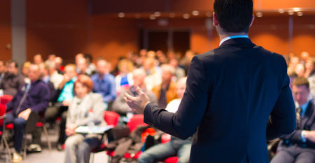 male speaker in front of large audience giving presentation
